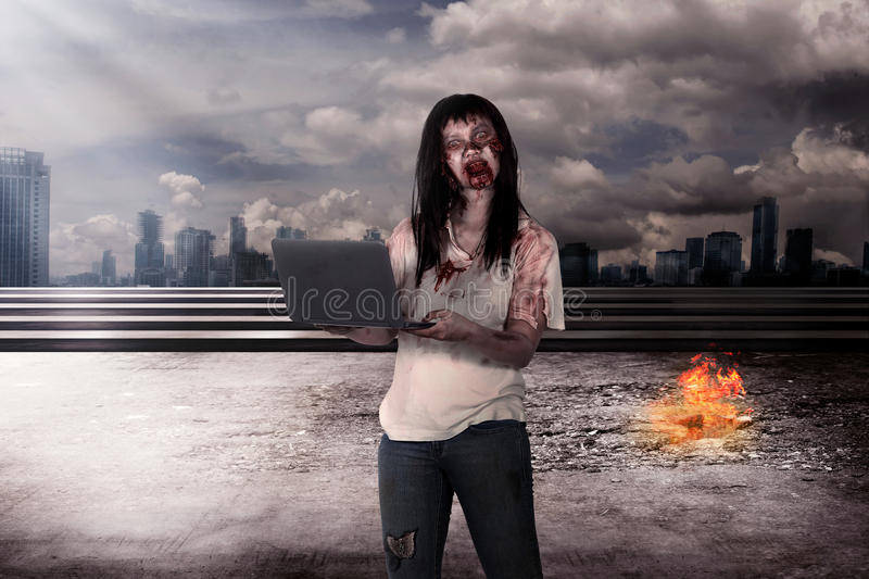 Female zombie holding laptop over burn city background. Halloween concept royalty free stock photography