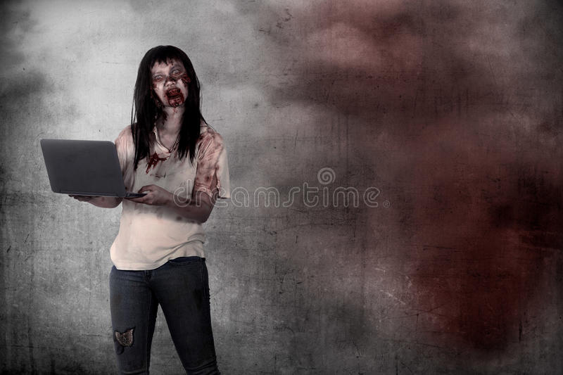 Female zombie holding laptop over grunge background. Halloween concept royalty free stock image