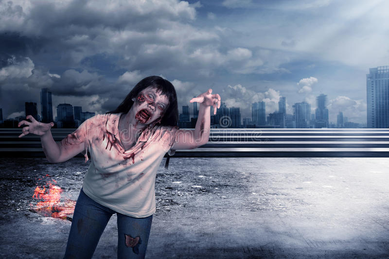 Female zombie over grunge background. Scary female zombie with burning city background. Halloween concept royalty free stock photo