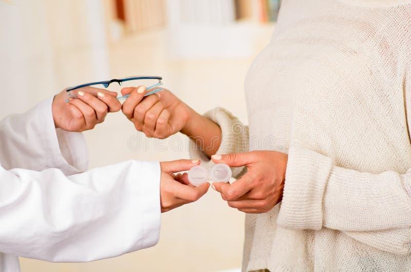 Femalee医生递给玻璃和隐形眼镜耐心提供的选择,眼力更正 眼科学 免版税库存照片