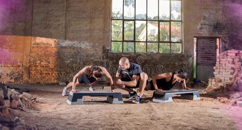 Females doing push-ups. Two female with trainer doing push-ups in hangar stock image