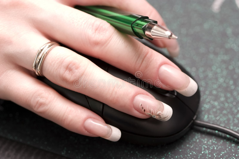 Females finger with nails. Womanish fingers with wonderful nails and pen from above mouse royalty free stock photography