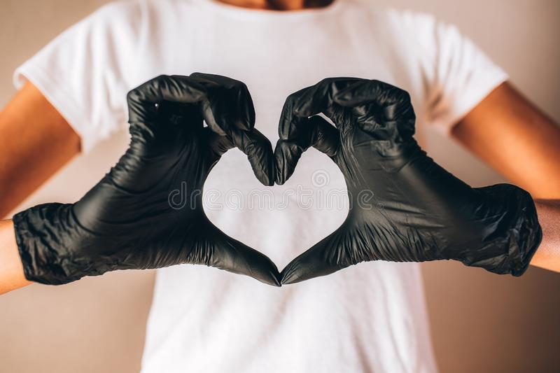 Females hands in black latex gloves show heart shape. Young slim tan woman in white tshirt and black gloves stock photo