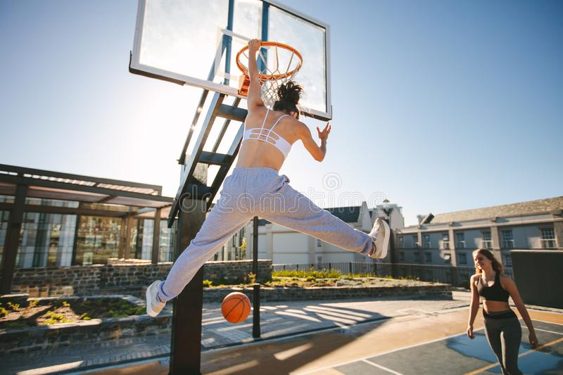 Females playing basketball on street court. Woman streetball player making slam dunk in a basketball game royalty free stock photos