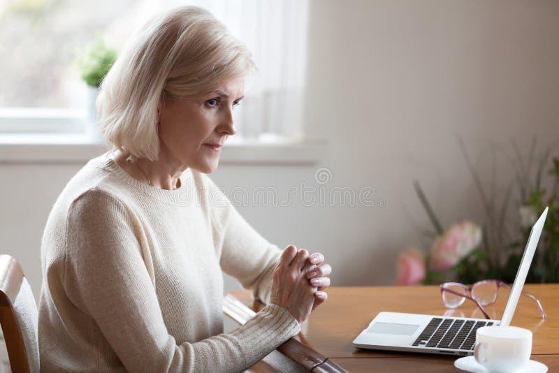 Femelle âgée réfléchie considérant quelque chose prenant la décision photo stock