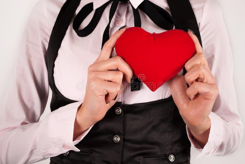 Femelle élégante avec le lien tenant le coeur rouge dans des mains images libres de droits