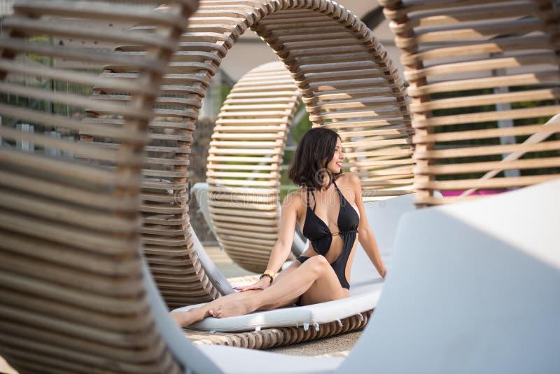 Femelle élégante avec un corps parfait se reposant dans le profil sur un canapé en bois sur le lieu de villégiature luxueux photos stock