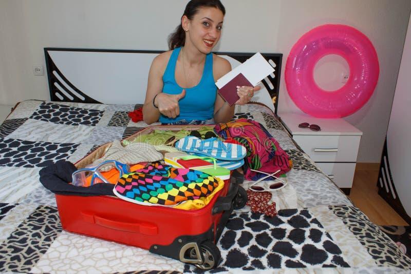 Femelle étant prête pour le déplacement jeune belle femme, valise rouge, séance, attendant, vacances d'été, AR colorée et voyagea photographie stock libre de droits