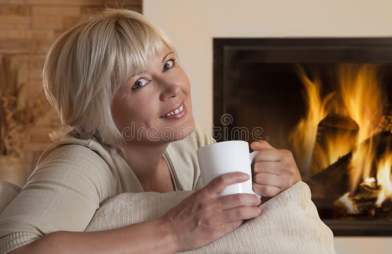 Femelle adulte appréciant la boisson chaude par la cheminée à la maison photo stock