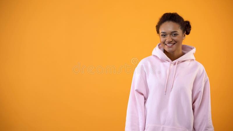 Femelle afro-américaine adolescente dans le hoodie surdimensionné sur le fond orange, mode images libres de droits