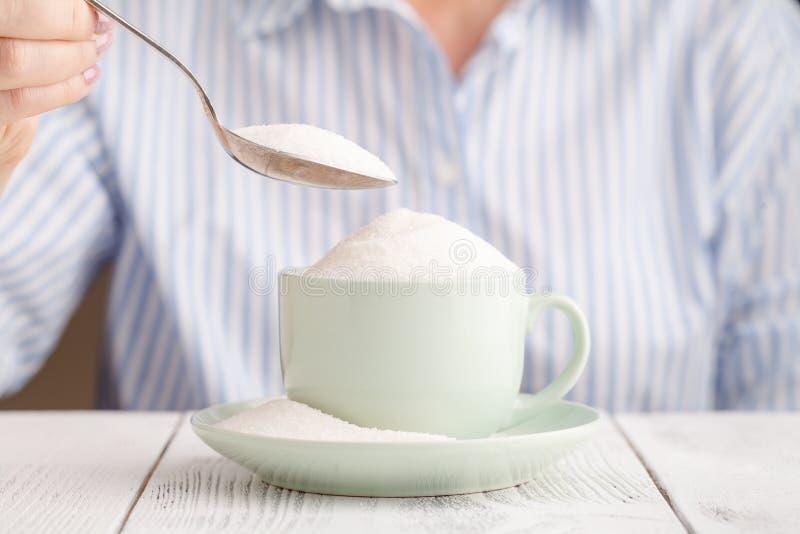 Femelle ajoutant beaucoup plus de sucre dans la tasse, risque de diabète, malsain photos libres de droits