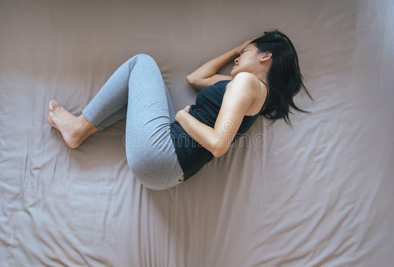 Femelle asiatique ayant le mal de ventre douloureux, femme souffrant de la douleur abdominale, crampes de période image libre de droits