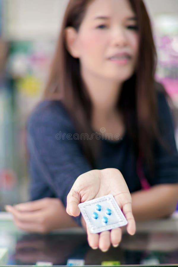 Femelle asiatique donnant le paquet de pilules bleues photo libre de droits