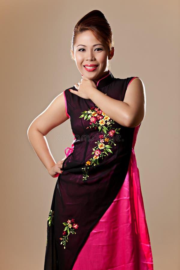 Femelle asiatique portant une robe rose de Vietnamien image stock