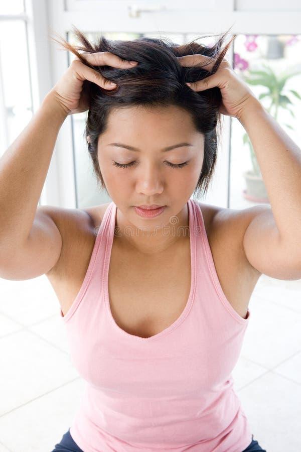Femelle asiatique se donnant le massage principal doux image libre de droits