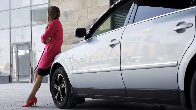 Femelle assez triste tenant l'automobile proche et attendant l'ami, solitude images stock