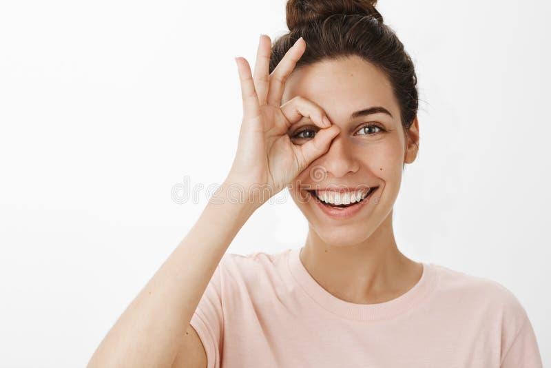 Femelle attirante à l'air amical heureuse sincère et aimable avec l'ok d'apparence de coiffure de petit pain ou signe zéro avec l photos libres de droits