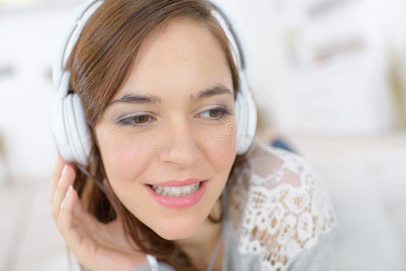 Femelle attirante de portrait de plan rapproché jeune avec des écouteurs photo stock