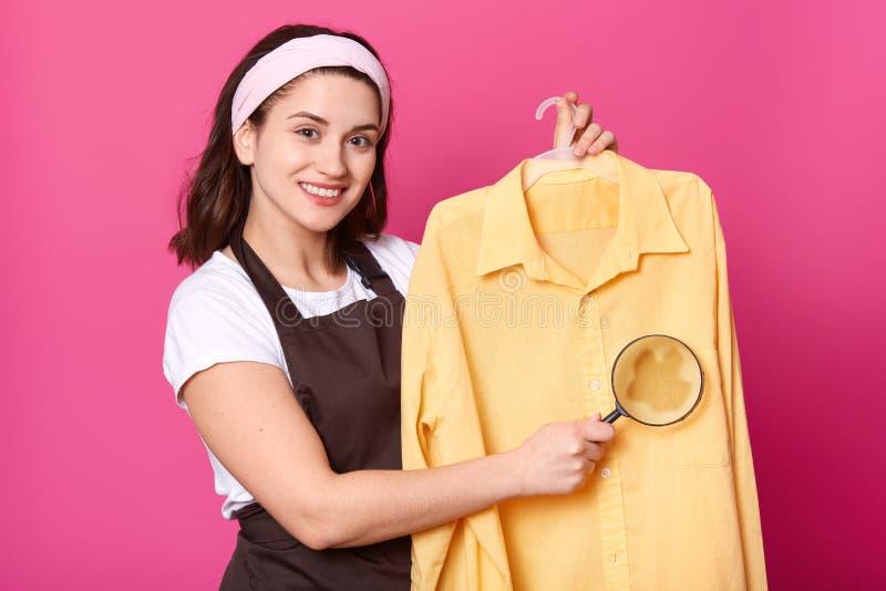 Femelle attirante de sourire avec le bandeau blanc tenant la chemise jaune-clair sur le cintre, regardant directement la caméra a image stock