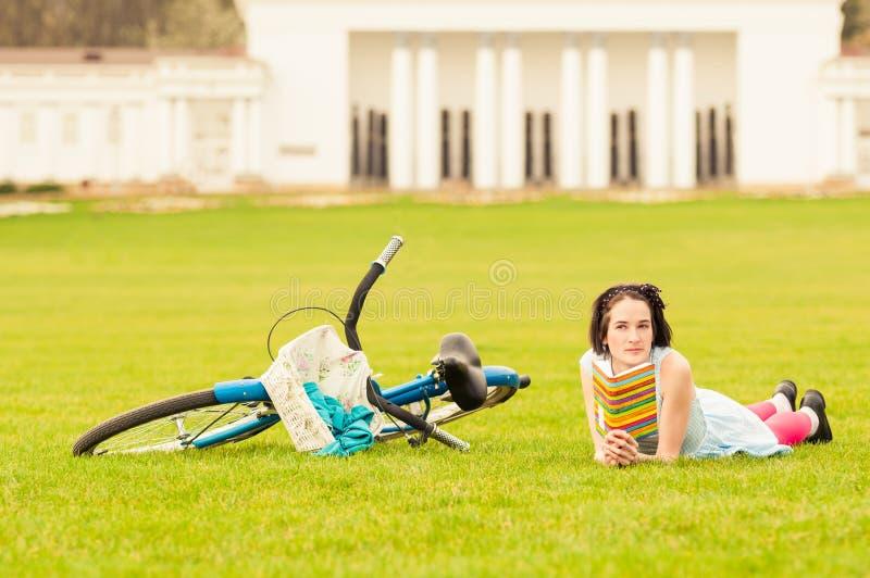 Femelle attirante lisant un livre près de la bicyclette de vintage images libres de droits