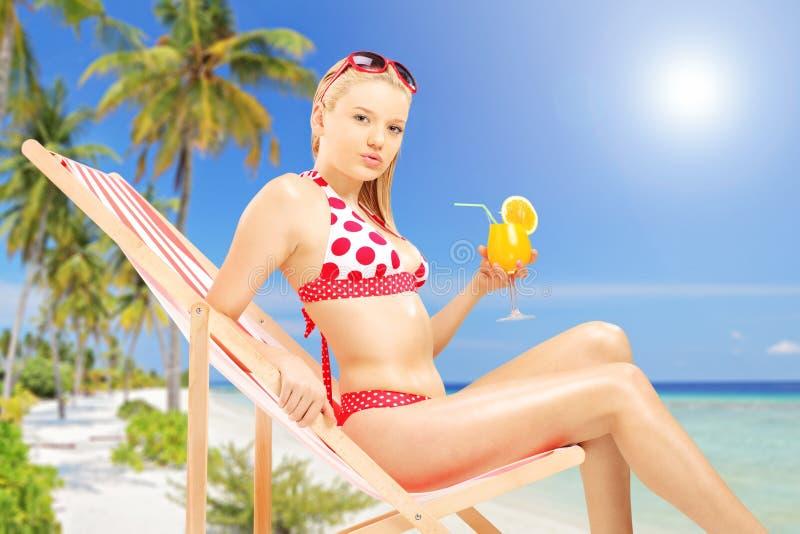 Femelle attirante tenant un cocktail et s'asseyant sur un salon de soleil photographie stock