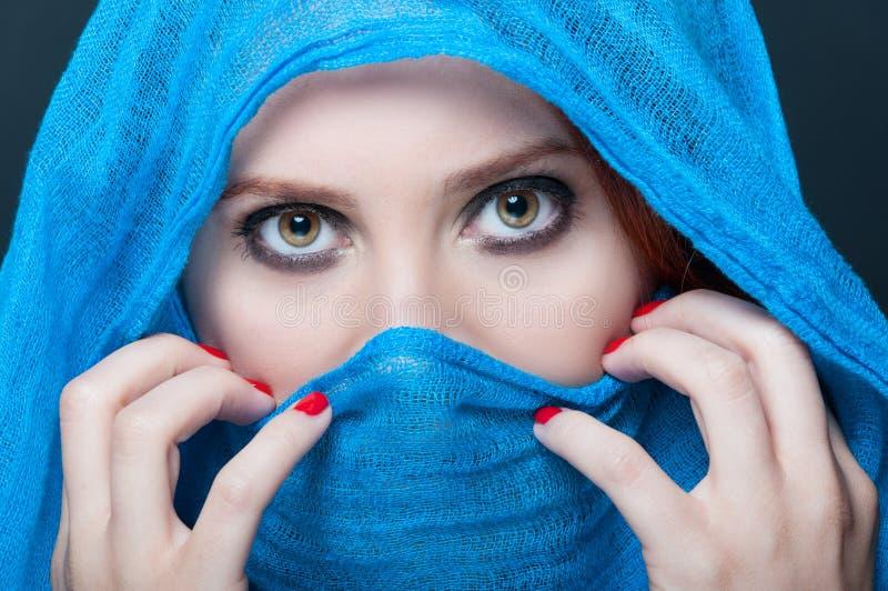 Femelle avec le burka bleu semblant mystérieux image libre de droits