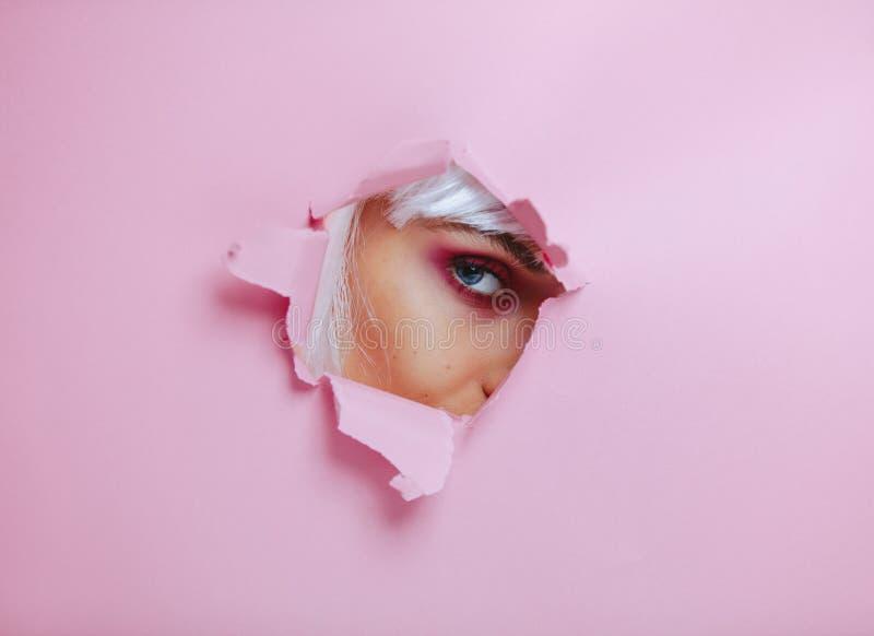 Femelle avec le maquillage d'oeil jetant un coup d'oeil par le papier déchiré photo libre de droits