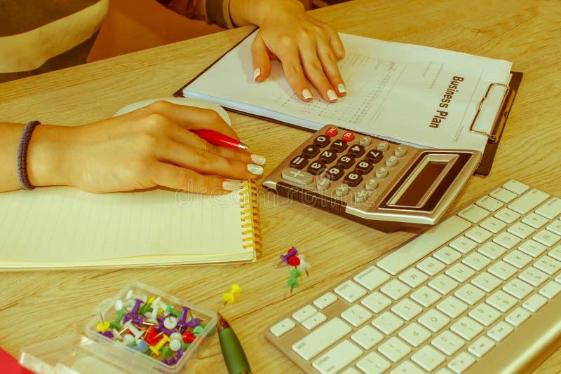 Femelle avec le plan d'action, la calculatrice et le stylo sur la table Femme travaillant dans le bureau, se reposant au bureau,  photos libres de droits