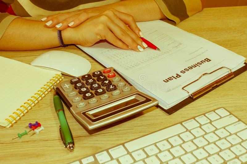 Femelle avec le plan d'action, la calculatrice et le stylo sur la table Femme travaillant dans le bureau, se reposant au bureau,  photographie stock libre de droits