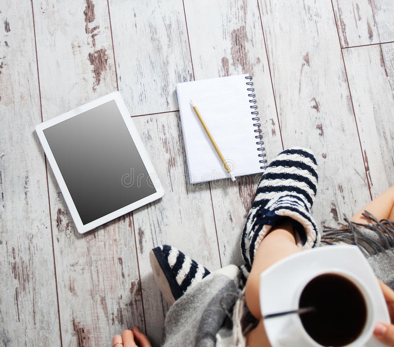 Femelle avec une tasse de café, de bloc-notes et de comprimé photographie stock libre de droits