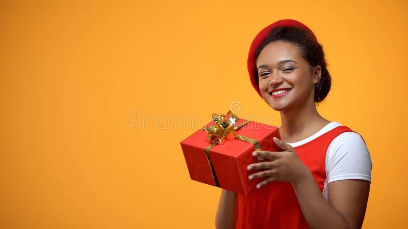 Femelle belle dans le béret rouge montrant le boîte-cadeau rouge, vente de vacances, célébration image libre de droits
