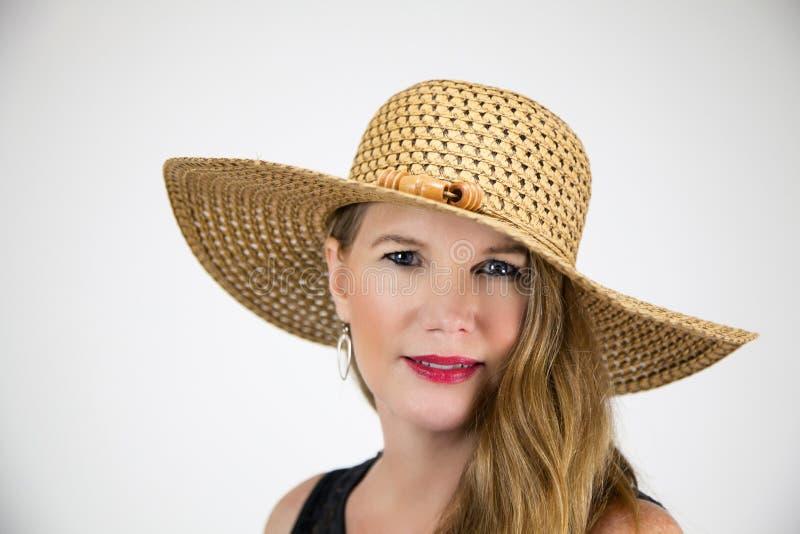Femelle blonde mûre de portrait de plan rapproché dans le chapeau et le dessus noir photo stock