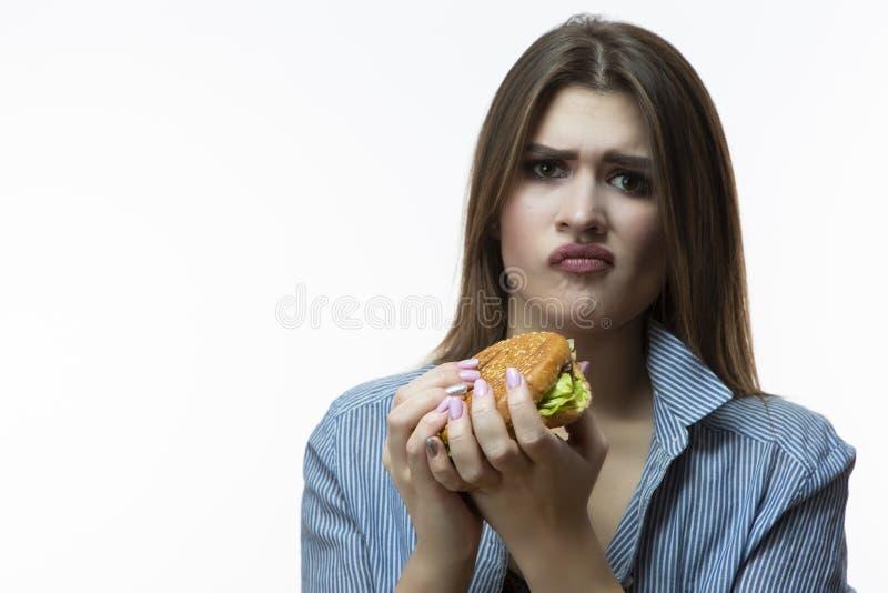 Femelle caucasienne contrariée et malheureuse avec l'hamburger ne voulant pas manger image stock