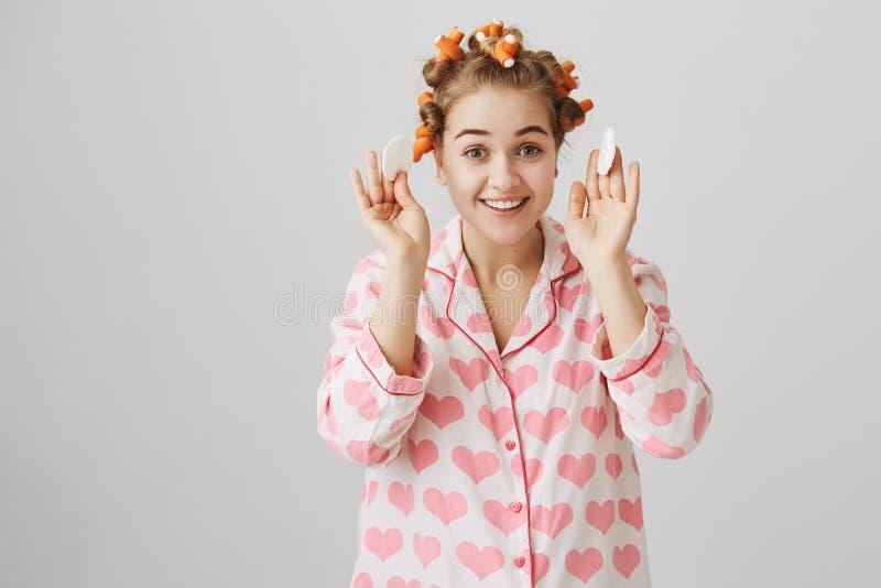 Femelle caucasienne heureuse émotive dans des pyjamas confortables avec des coeurs, des bigoudis de cheveux de port et tenir deux photos libres de droits