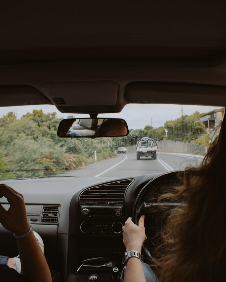 Femelle conduisant une voiture avec son ami s'asseyant à côté de son tir de l'intérieur images libres de droits