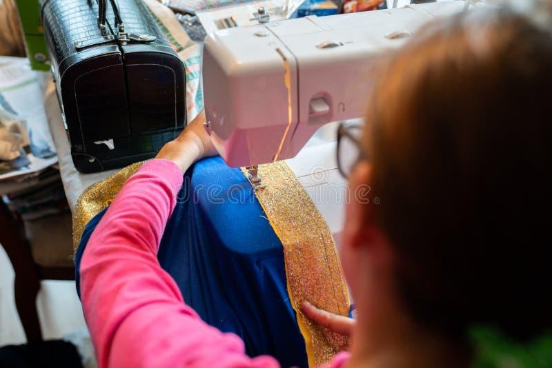 Femelle cousant un costume d'enfant de Halloween sur la machine images stock