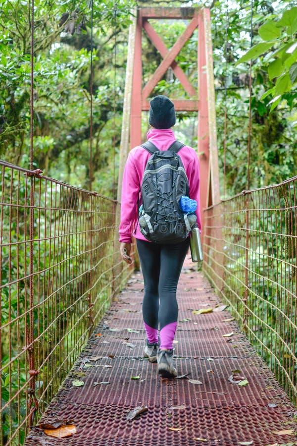 Femelle croisant un pont suspendu photo libre de droits