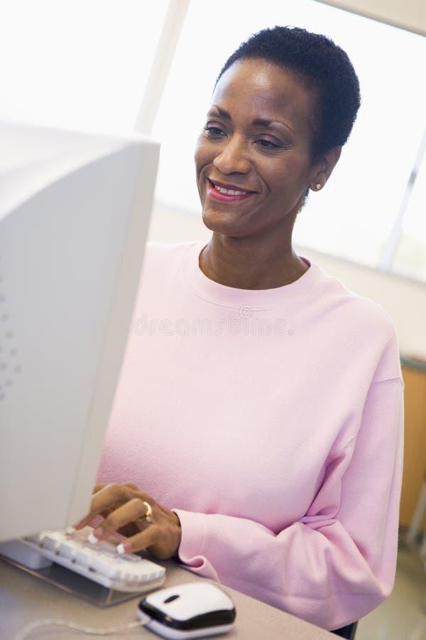 femelle d'ordinateur apprenant l'étudiant mûr de qualifications photo libre de droits