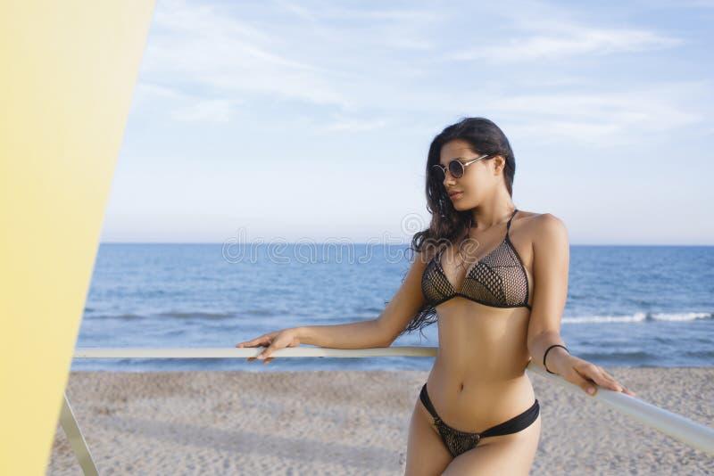 Femelle dans le bikini à la mode se reposant près de la mer après promenade dans le jour ensoleillé photographie stock libre de droits