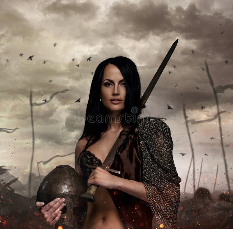 Femelle dans le costume de guerre tenant l'épée et le casque photographie stock libre de droits
