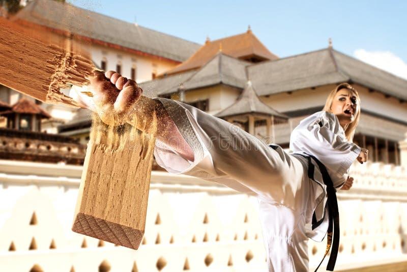 Femelle dans le kimono pratiquant le Taekwondo Rupture du conseil image libre de droits