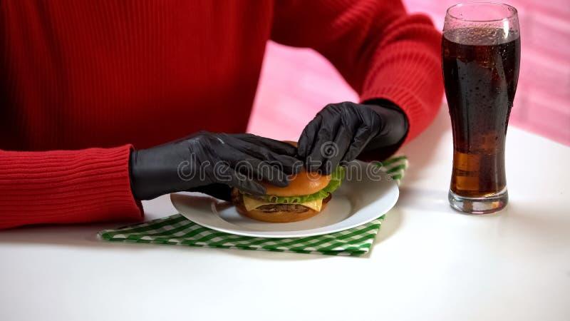 Femelle dans les gants en caoutchouc noirs tenant l'hamburger savoureux et buvant l'eau de seltz image libre de droits