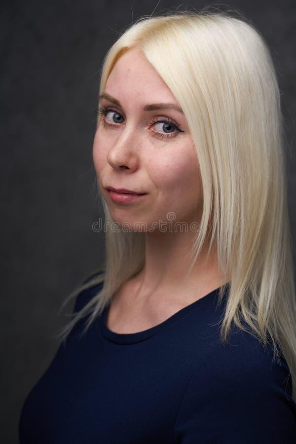 Femelle de beauté blonde dans des vêtements sport noirs sur le fond gris images libres de droits
