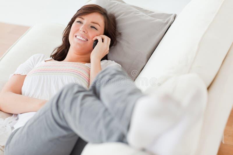 Femelle de Brunette au téléphone se trouvant sur un sofa photo stock