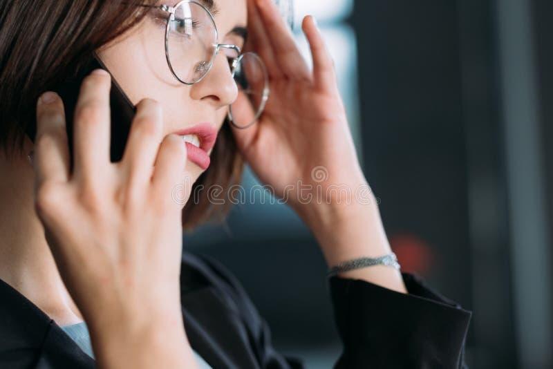Femelle de conversation téléphonique sérieuse de travail de coupure jeune photo stock