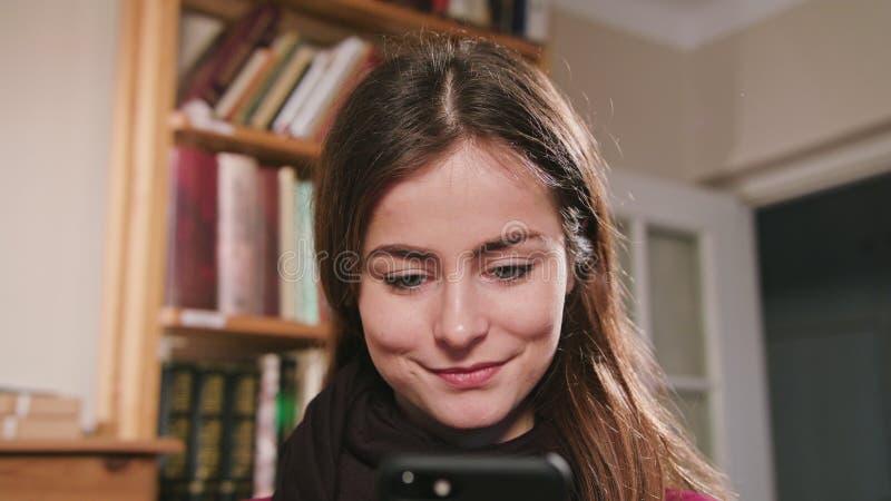 Femelle de sourire à l'aide du téléphone photos libres de droits