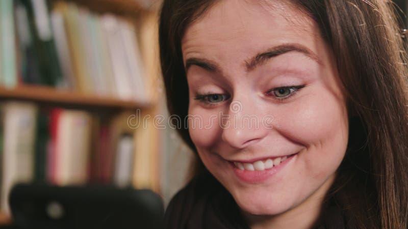 Femelle de sourire à l'aide du téléphone photo stock