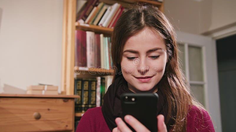 Femelle de sourire à l'aide du téléphone images libres de droits
