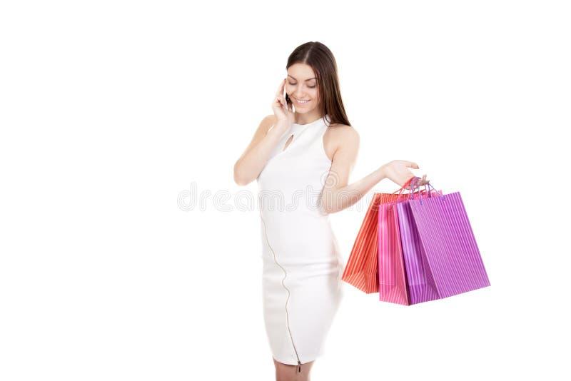 Femelle de sourire à l'aide du téléphone portable se tenant avec des achats colorés photos stock