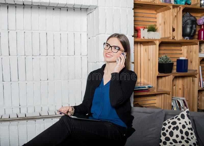 Femelle de sourire en verres ayant la conversation téléphonique de cellules par l'intermédiaire du téléphone portable tout en se  photos stock